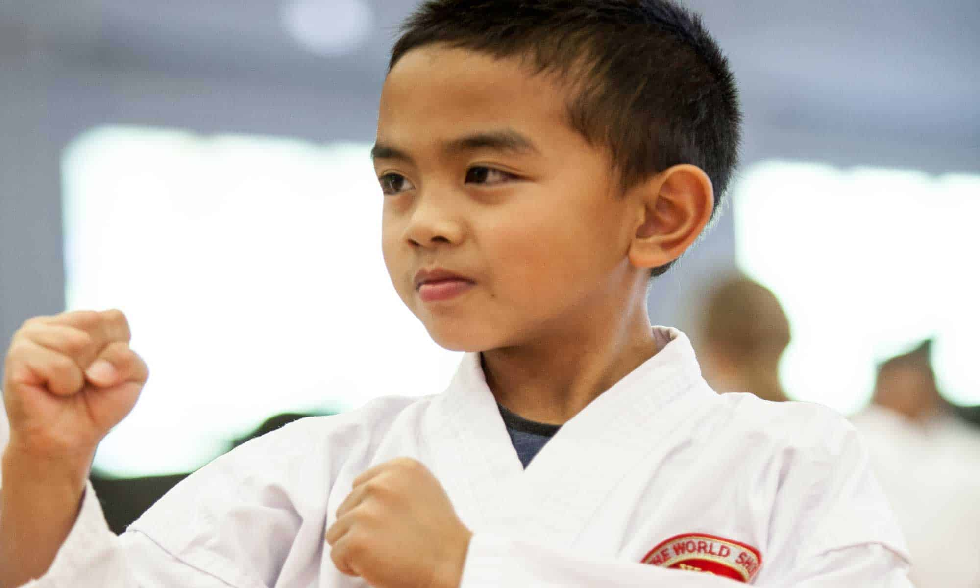 young boy with his fists up defensively looking to the left of the camera